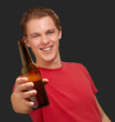 portrait of young man holding beer over black background