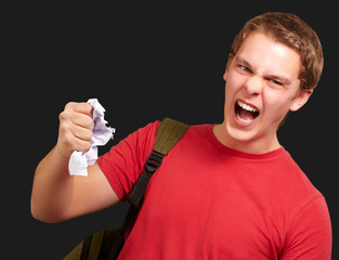young angry student man roughing a sheet over black background