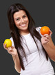 young pretty girl holding orange and lemon over black background