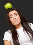 portrait of young woman holding green apple on her head over bla