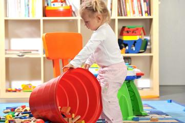 Kleines Mädchen sitzt in Spielzeugeimer