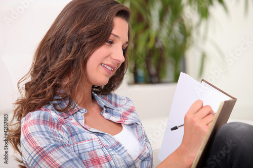Woman scoring in notebook