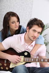 Young woman and young man with guitar