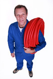 Plumber with large reel of red flexible pipe