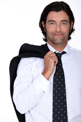 Smiling businessman with his jacket over his shoulder