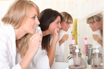 Three women brushing their teeth