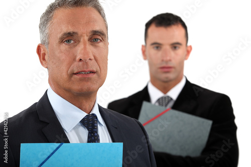 businessman with his assistant trailing behind him