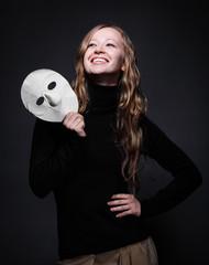 Low key portrait of a beautiful woman holding mask