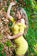 Young attractive girl with yellow dress outdoor on the field
