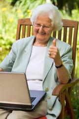 ältere Frau im Garten mit Laptop