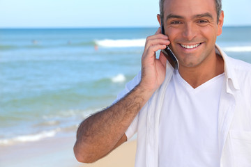 Man taking a call whilst at the beach