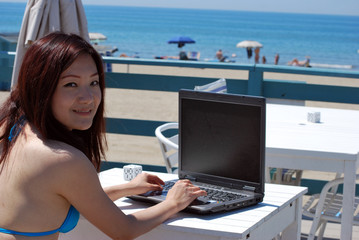 Asian girl on the beach with laptop3