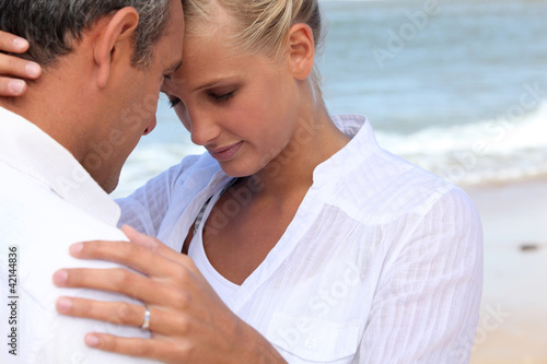Affectionate couple dressed in white at the seaside