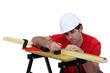 Carpenter marking wood before planing