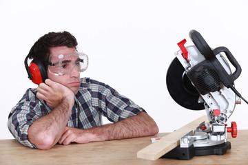Bored man looking at circular saw