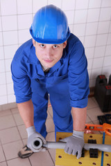 Plumber preparing to cut piece of pipe