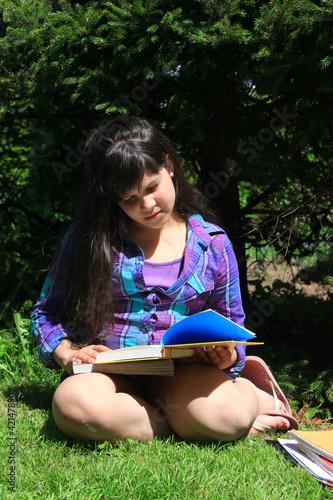 Young girl doing homework outdoors