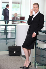 Smiling female executive using a mobile in the office