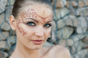 A young woman with a body-art on the face