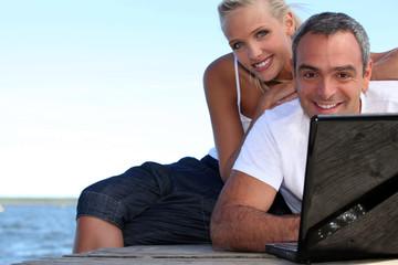 a couple on a pontoon near the sea, the man is doing computer,
