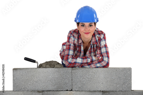 female bricklayer with arms resting on concrete wall
