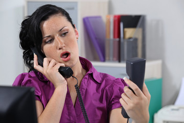 Annoyed receptionist answering ringing phones