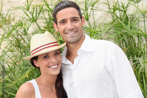 Couple in front of green branches