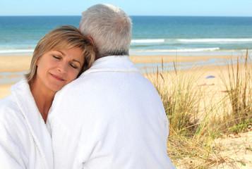 Mature couple in bathrobe on the beach