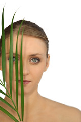 Woman in makeup holding a leaf in front of her face