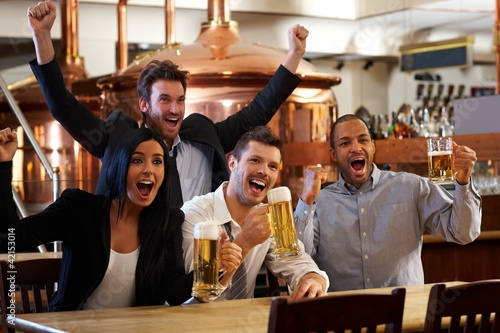 Happy fans watching TV in pub cheering