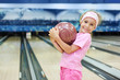 Little girl dressed in pink T-shirt holds ball in bowling club
