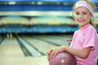 Little girl  sits and holds ball in bowling club