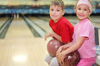 Happy brother and sister sit and hold balls in bowling club