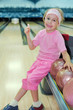 Smiling girl  sits and thumbs up in bowling club
