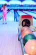 Girl prepares to throw ball in bowling; Focus on number of balls