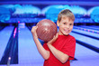 Little smiling boy holds ball in bowling club