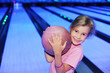 Smiling little girl holds ball in bowling club