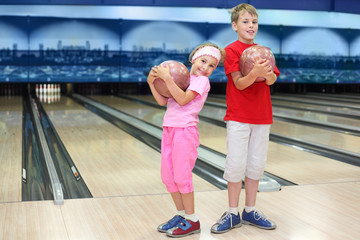Smiling brother and sister hold balls in bowling club