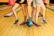 Legs of young man and two girls with balls in bowling club