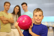 Smiling boy dressed in T-shirt holds pink ball in bowling club