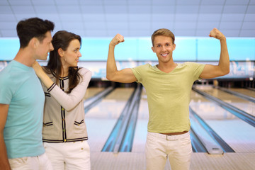Smiling man shows arm muscles; pair look at him in bowling club;