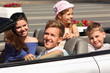 Happy father, mother and two children ride in convertible car