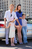 Young, mother and two happy children stand near convertible car