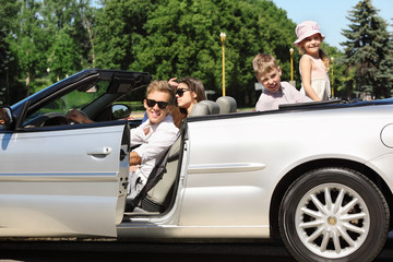 Happy father, mother and two children sit in convertible car