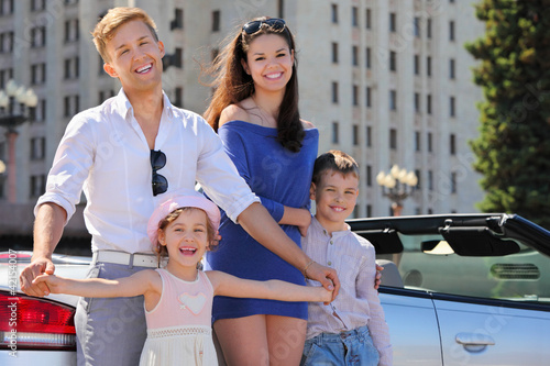 Smiling father, mother and two children stand near car