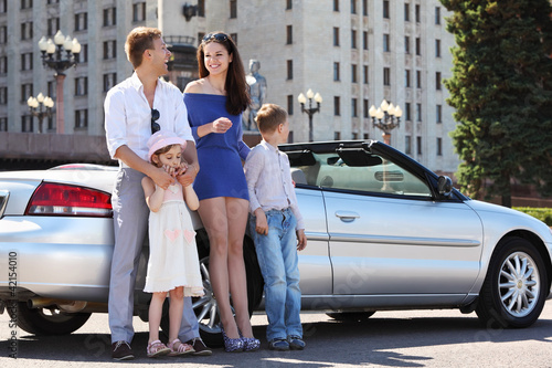 Happy father, mother and two children stand near convertible car