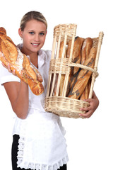 Bakery worker holding basket of bread