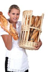 Bakery worker holding basket of bread