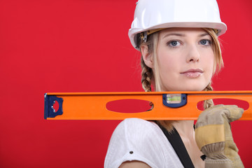 craftswoman holding ruler against red background
