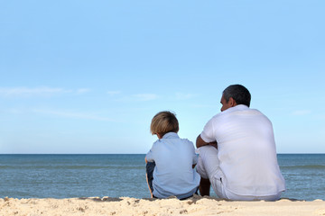 Father and son sitting on the edge of the ocean
